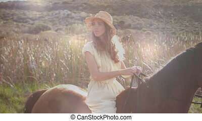 Woman riding a horse in the flower field