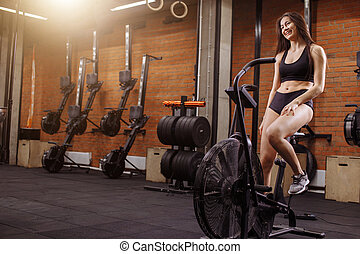 woman riding an exercise bike in gym. fit girl doing cardio training on bicycle