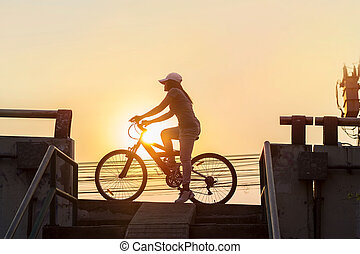 Woman riding bicycle, exercising in sunset town