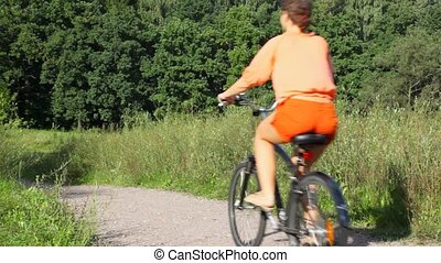 woman riding bicycle from camera in park