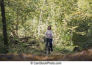 Woman riding bicycle in forest