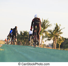 woman riding bicycle on green track with beautiful rider suit