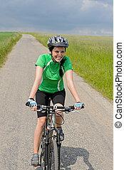 Woman riding bike on cycling path meadow