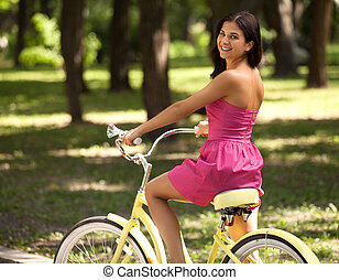 Woman riding bike. Side view of cheerful young woman riding bike in spring park