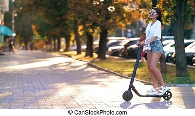 Woman riding electric scooter in the city