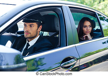 Woman riding in a car with chauffeur - Beautiful woman...