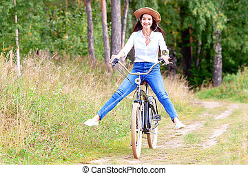 Woman riding on a bicycle in a summer park or forest
