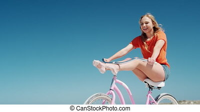 Woman riding on her bike on the beach