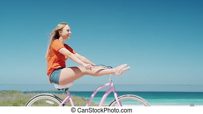 Woman riding on her bike on the beach - Side view of a happy...