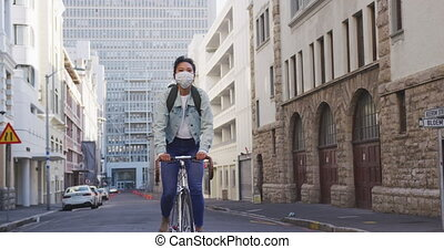Front view of a mixed race woman with long dark hair out and about in the city streets during the day, wearing a face mask against air pollution and coronavirus, riding on her bicycle with buildings in the background in slow motion.
