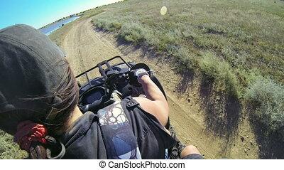 Woman riding quad POV - Woman riding quad bike on a dusty...