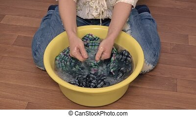 Woman rinse clothes in bowl on the floor