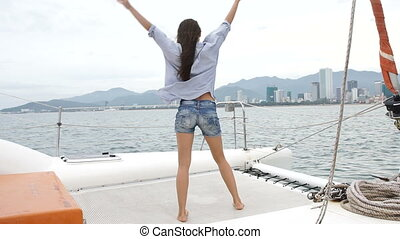 Woman rise hands and dancing while enjoying a cruise on yacht