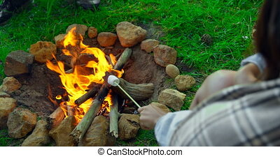 Woman roasting marshmallow on campfire 4k - Woman roasting ...