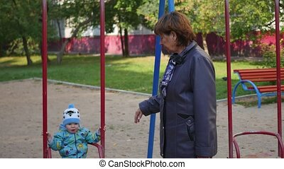 woman rocking her child on a swing on a Sunny summer day