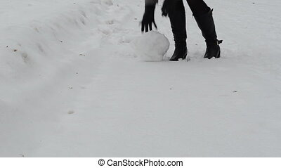 woman roll snowball - woman rolling snowball snow ball to...