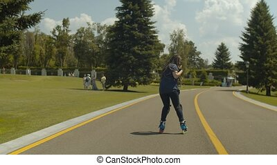 Young carefree joyfiul female showing skill of backward rollerblading at good speed on public park footpath. Active woman in protective equipment rollerskating over nature landscape background.