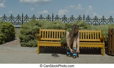 Stylish female with long ponytail from afro-braids unfastening and taking roller skates off while sitting on park bench after ride. Young woman roller going to relax after workout in public park.