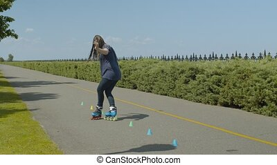 Positive skillful female roller riding crisscross backwards and forwards across cones standing in line on park footpath. Active woman training inline skating while rolleblading in summer park.