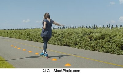 Back view of skillful female roller skating crisscross through cones in public park. Stylish roller woman with ponytail from afro-braids practicing inline slalom backwards during training outdoors.
