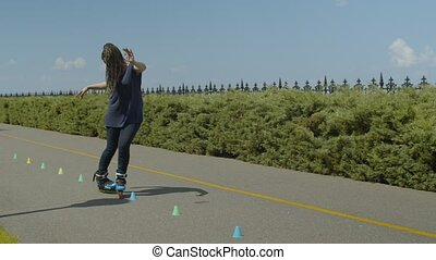 Woman rollerblading backward through cones outdoor -...