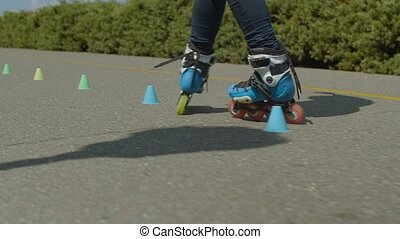 Woman roller's feet riding round cones in park - Back view...