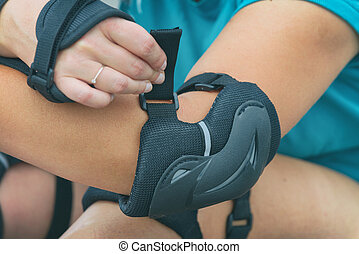Woman rollerskater putting on elbow protector pads on her...