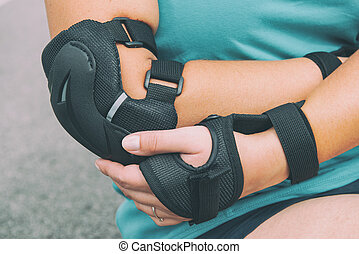 Woman rollerskater with elbow protector pads on her hand and...
