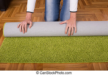 Woman rolling carpet - Close up of female hands rolling...