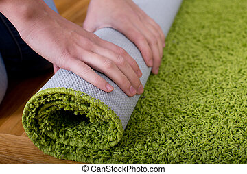 Woman rolling carpet - Close up of female hands rolling ...