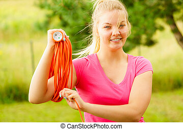 Woman rolling up extension cord