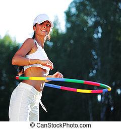 hula hoop - woman rotates hula hoop on nature background