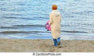 woman rotating girl on sandy beach