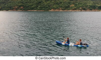 Woman Rowing Kayak with Man Sitting Behind - Woman rowing ...