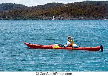 Woman rows a sea kayak
