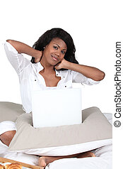 Woman rubbing her neck while using a laptop on her bed