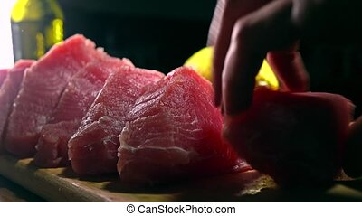 Woman rubbing tuna fillet pieces with ginger marinade. 4K...