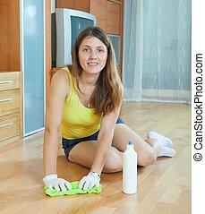 woman rubbing wooden floor