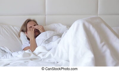 Woman rubs eyes in a bed