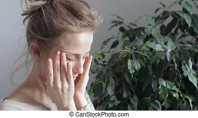 Woman rubs her eyes