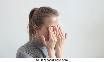 Woman rubs her eyes - Tired beautiful woman rubs her eyes at...