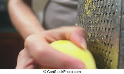 woman rubs on grated lemon peel, close-up, slow-motion...