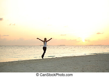 woman run along the sea coast of sunrise behind