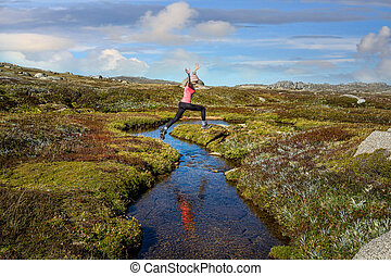 Woman run free jumping little meandering  stream in high ...