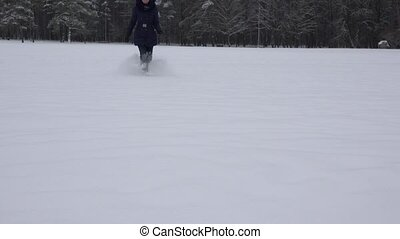 woman run through loose snow winter time. Freetime outdoor....