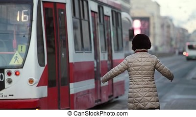 Woman runing for a tram at cloudy day