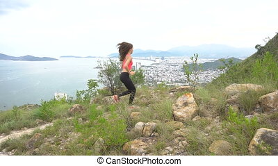 Woman runner happy and celebrating success. Female run on top of the mountain, cheering in winning gesture.