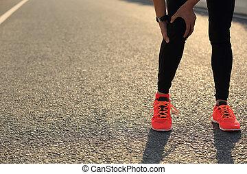 woman runner hold her injured leg on road