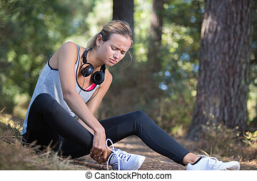 woman runner hold her sports injured ankle