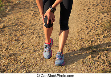 woman runner hold her sports injured knee on dirt road